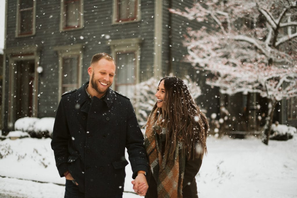 A couple laughing, walking through a historic neighborhood in Indianapolis as big snowflakes fall around them.