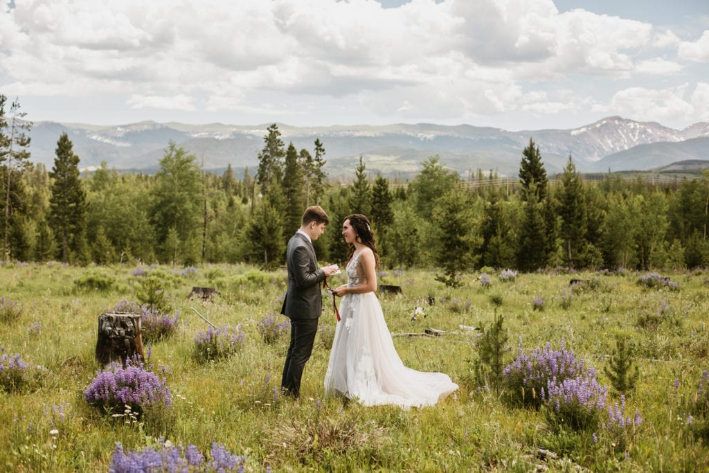 Couple reading their vows to each other on the mountainside in Colorado before their Rocky Mountain National Park ceremony.