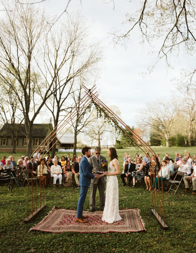 Bride and groom standing under their handmade arch during their cozy, intimate ceremony in Franklin, Tennessee