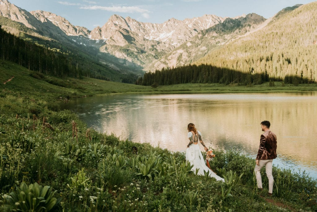 bride and groom walking near lake and mountains after their national park wedding ceremomy