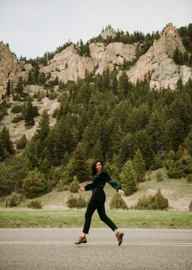 A girl running and laughing in front of mountains in Paradise Valley, Montana.