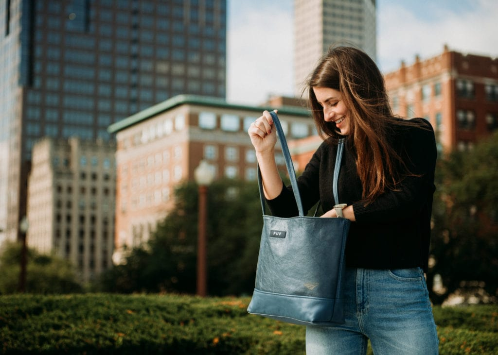 Girl holding a leather bag in a city