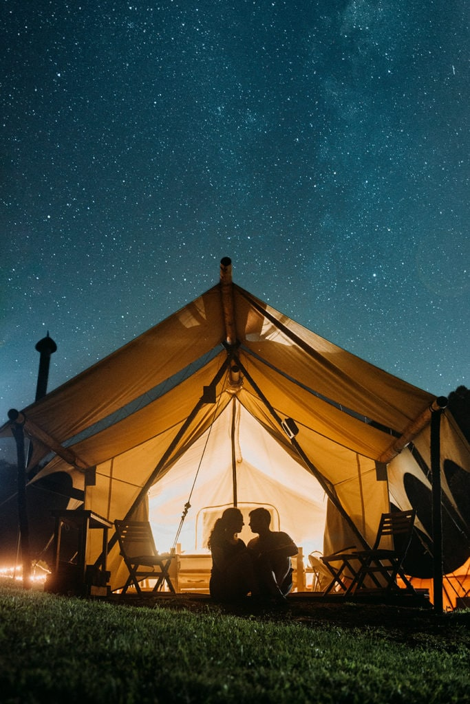 A couple stargazes from their tent at Under Canvas in Great Smoky Mountains National Park.