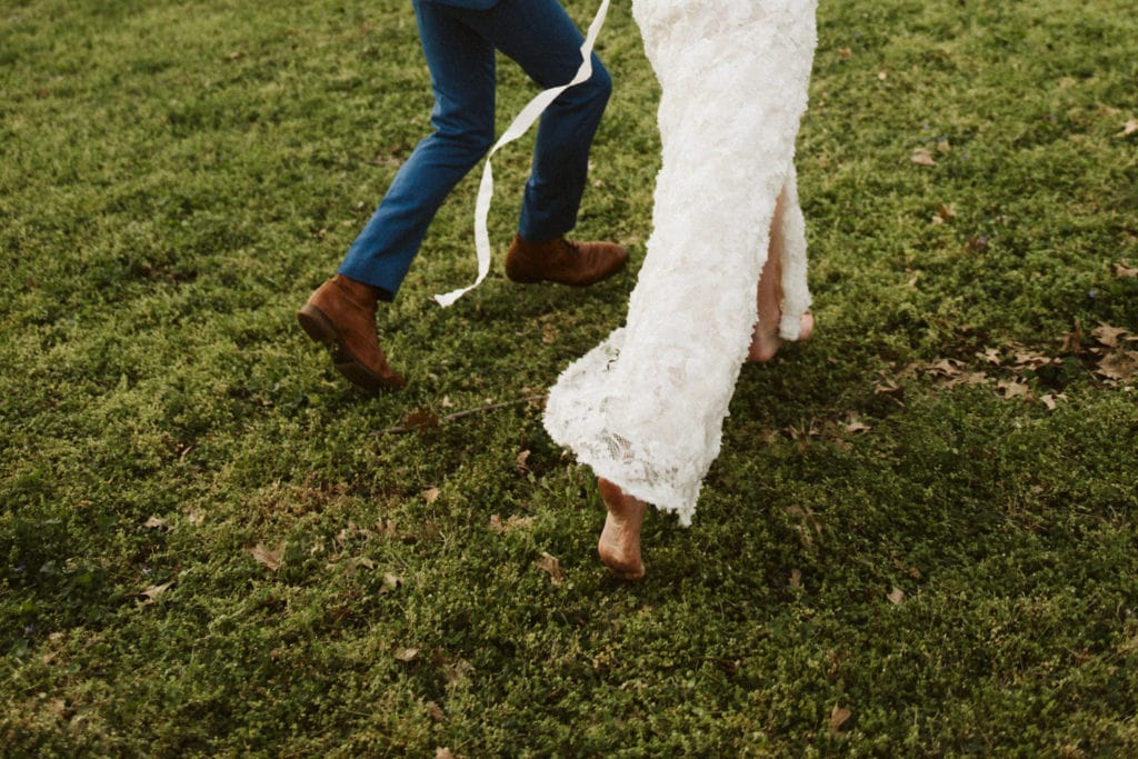 A barefoot bride and her new husband running after their intimate backyard wedding in Franklin, Tennessee. The bottom of her feet are a little bit dirty, and her dress and bridal belt are flowing behind her.
