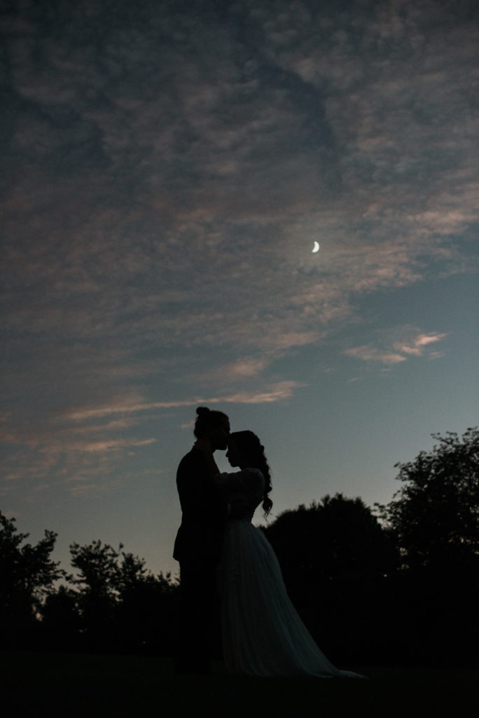 Nighttime silhouette of a groom kissing his bride's forehead with the moon glowing above them. Taken the day of their intimate woodland wedding in Indiana.