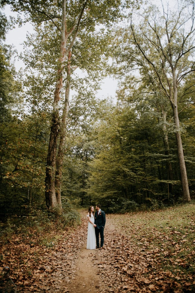 A bride and groom stand in the woods holding hands after their adventure forest wedding in Brown County Indiana. A perfect selection of colors are surrounding them during their small wedding in the fall.