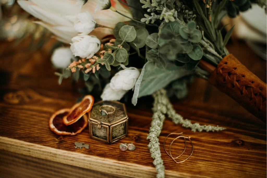 Detail shot of a handmade bridal bouquet with wedding rings, earrings and a gold ring box sitting on a table at the Wilds Venue in Bloomington, Indiana.