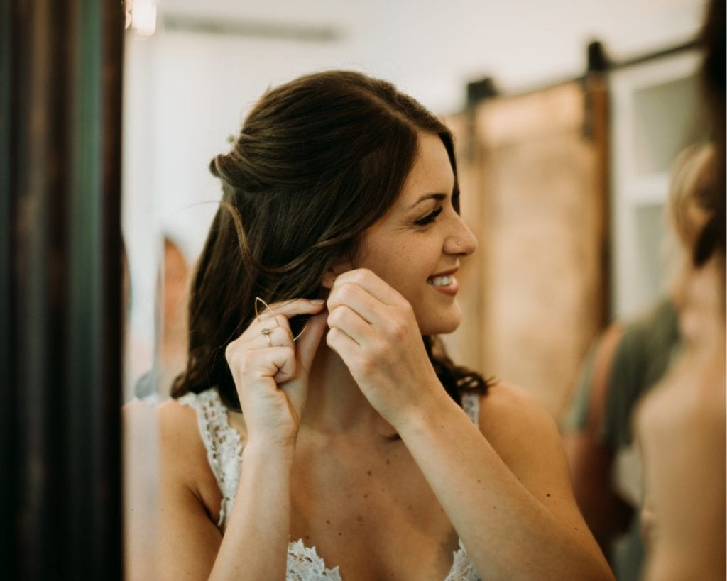 Bride putting her Katie Carder earrings in and getting ready for her wedding ceremony at the Wilds Venue in Bloomington, Indiana in the bridal suite.