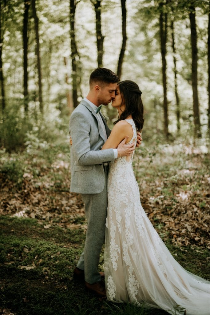 The sweetest first look in the forest before a wedding ceremony at the Wilds Venue in Bloomington, Indiana. The couple is embracing as light dapples the forest floor around them.