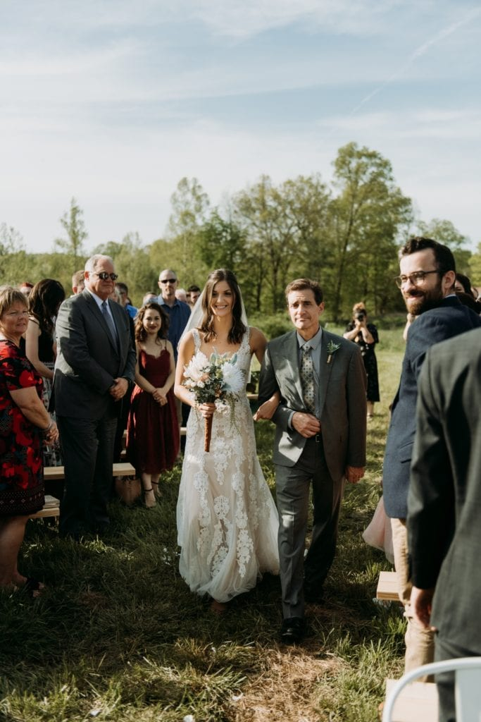 Bride walking down the aisle with her father during a summer outdoor wedding ceremony at the Wilds Venue.