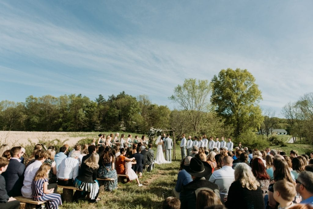 Wide angle shot of bride and groom holding hands during the ceremony, they're standing under their handmade wooden ceremony arch decorated with florals, during their outdoor wedding ceremony in the summer at The Wilds Venue in Bloomington, Indiana. Lush trees and a field and a lake are in the background, a perfect setting for an intimate summer wedding.