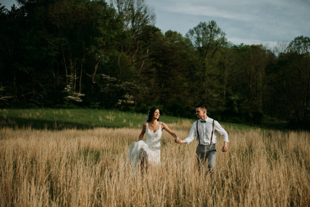 Bride and groom holding hands and running through a field as the sun begins to set. Right after their emotional and heartfelt intimate ceremony at the Wilds Venue in Bloomington, Indiana.