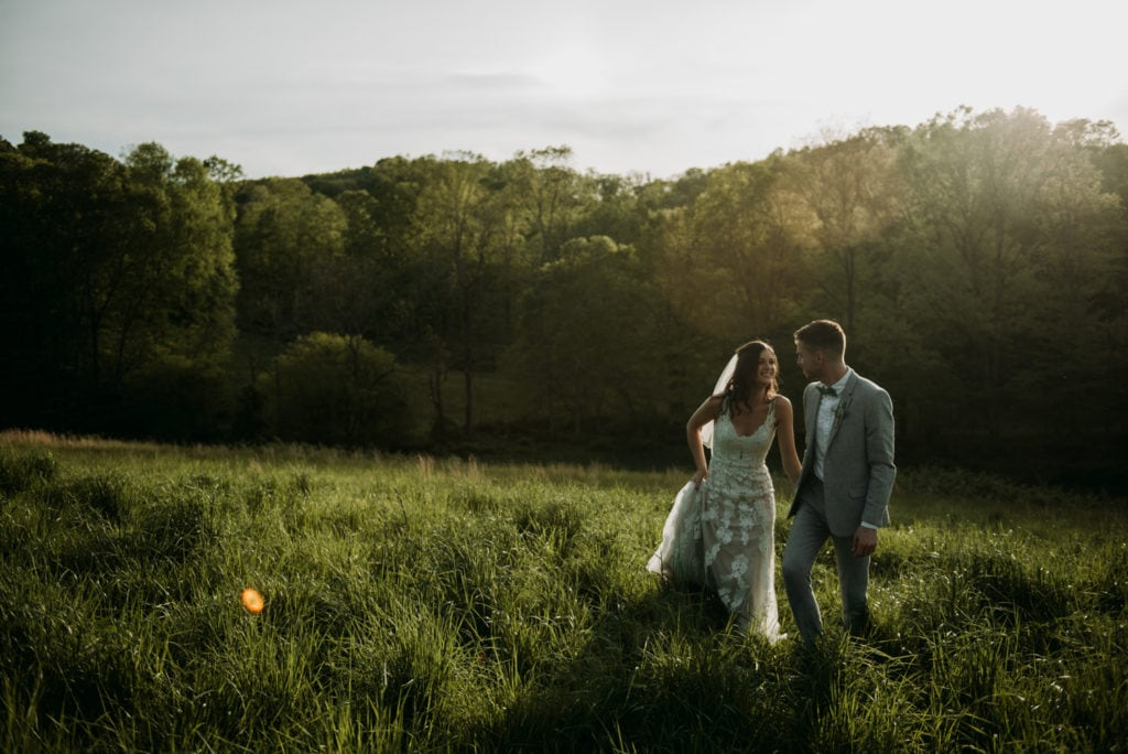 Bride and groom holding hands and walking near an overlook as the sun is setting behind them. Right after their emotional and heartfelt intimate ceremony at the Wilds Venue in Bloomington, Indiana.
