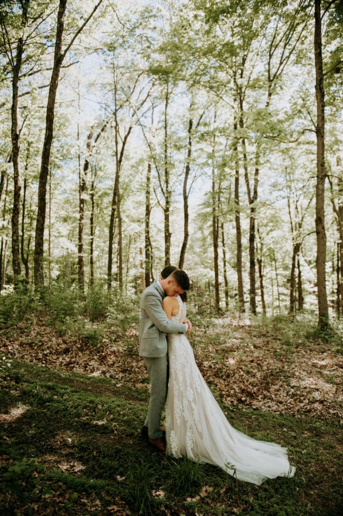 Newlyweds embracing in a forest during their first look before their intimate heartfelt ceremony in Bloomington, Indiana at the Wilds Venue.