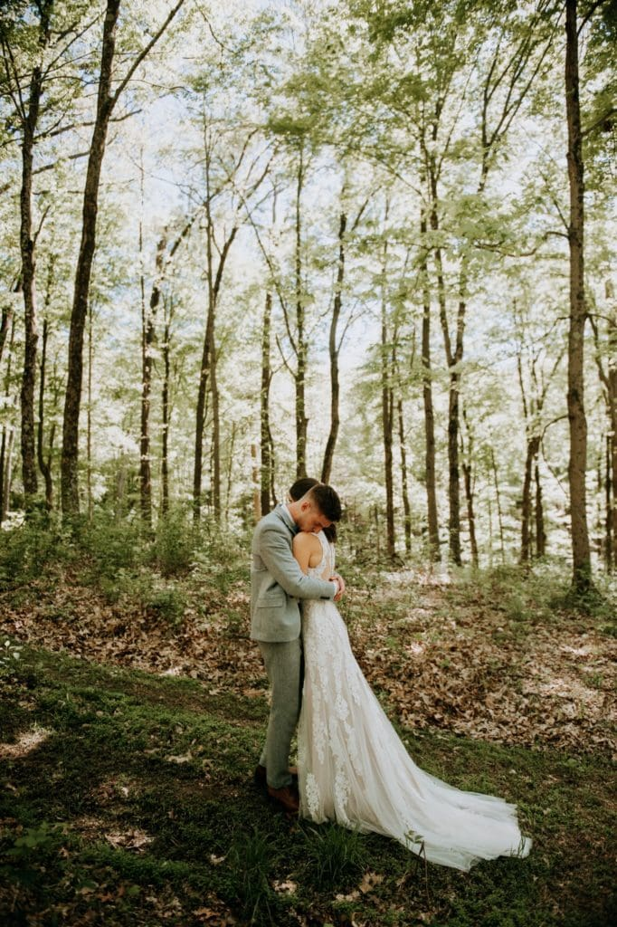 The sweetest first look in the forest before a wedding ceremony at the Wilds Venue in Bloomington, Indiana. The bride and groom are embracing each other as light dapples the forest floor around them.