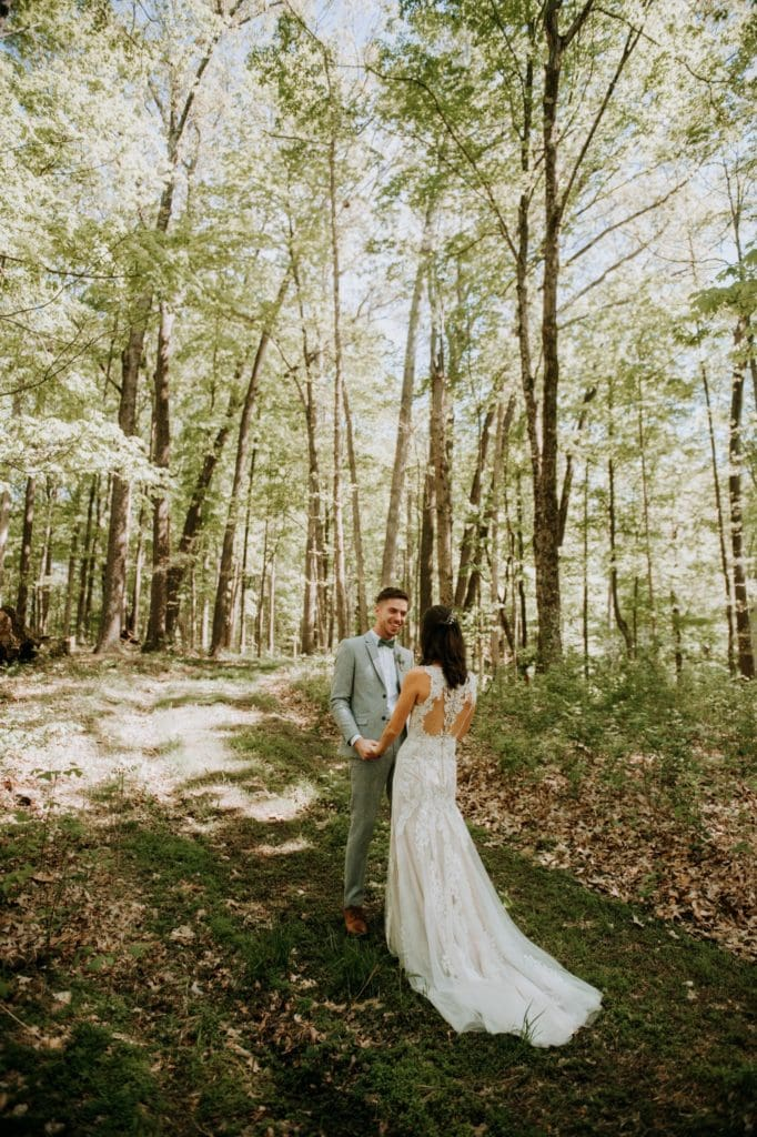 The sweetest first look in the forest before a wedding ceremony at the Wilds Venue in Bloomington, Indiana. The bride and groom are holding and hands and looking at each other as light dapples the forest floor around them.
