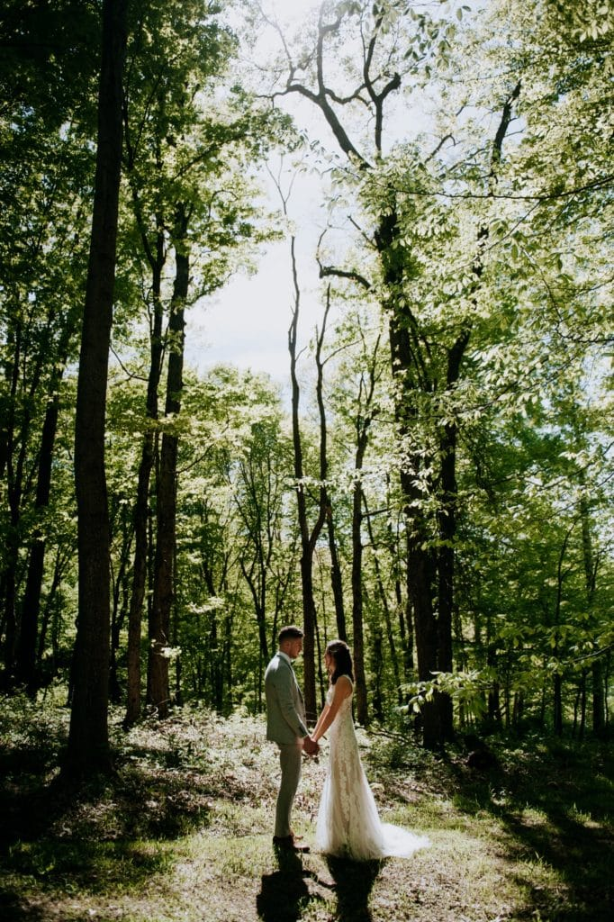 The sweetest first look in the forest before a wedding ceremony at the Wilds Venue in Bloomington, Indiana. The bride and groom are holding hands and looking at each other, standing in the light coming through the trees.