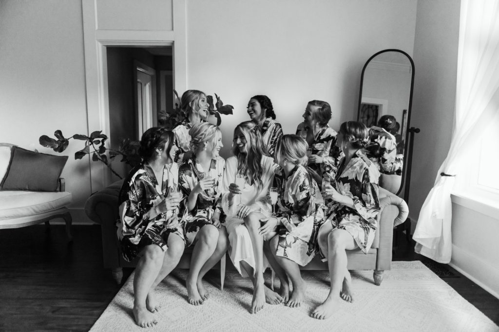 A bride and her bridesmaids in their matching robes, clinking their champagne glasses, and sitting on a couch in the bridal suite at Mustard Seed Gardens in Indiana