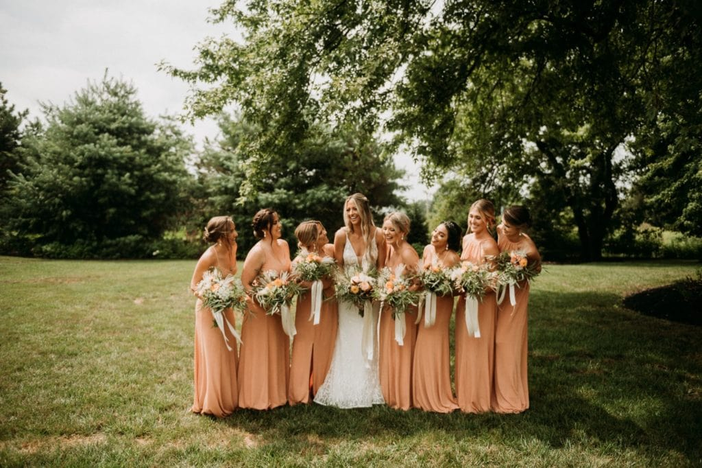 Summer bridesmaids photos in peachy colored dresses at Mustard Seed Gardens. Boho bridesmaids dresses perfect for summer.
