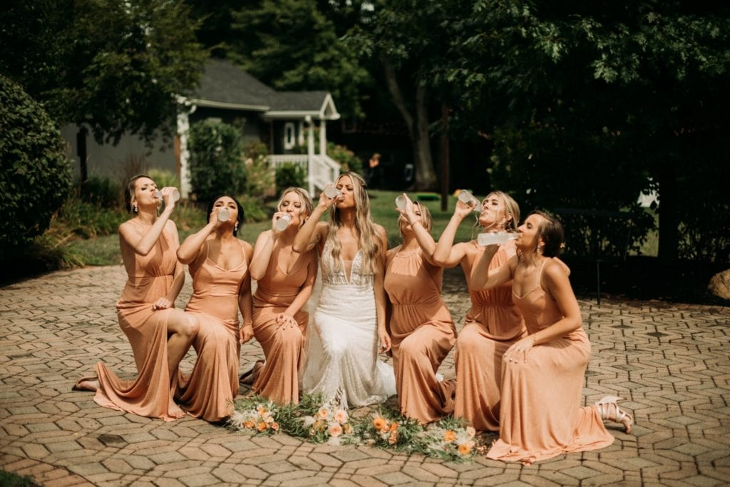 Summer bridesmaids photos in peachy colored dresses at Mustard Seed Gardens. Bridesmaids are all drinking a Smirnoff Ice