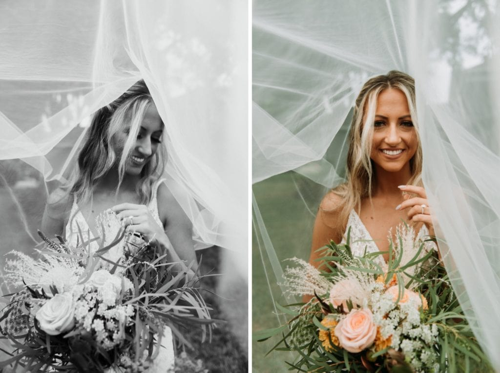Boho bridal portraits under the veil. The bride is in the middle of the frame, holding her bouquet and smiling before the wedding ceremony at Mustard Seed Gardens.