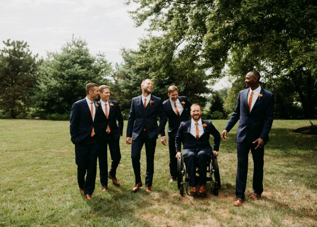 Groomsmen photos before the wedding ceremony at Mustard Seed Gardens. The groomsmen are wearing navy suits with orange ties and boutonnieres.
