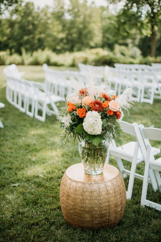 A vase of orange and white flowers sitting next to lined up chairs ready for the wedding ceremony about to happen at Mustard Seed Gardens.