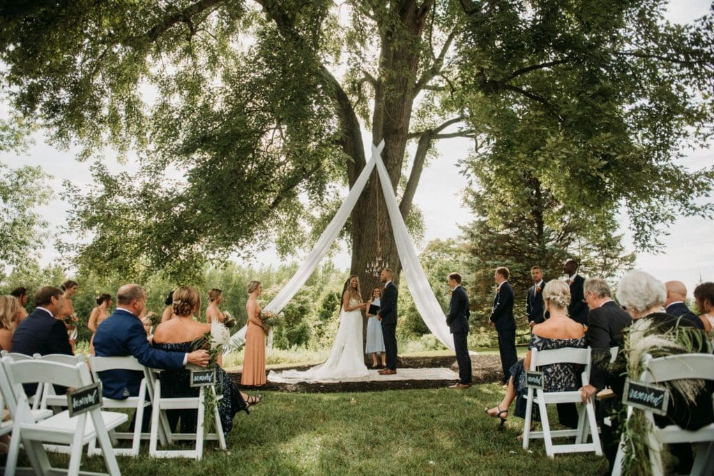 Bride and groom standing underneath a large oak tree during their boho summer wedding ceremony at Mustard Seed Gardens.