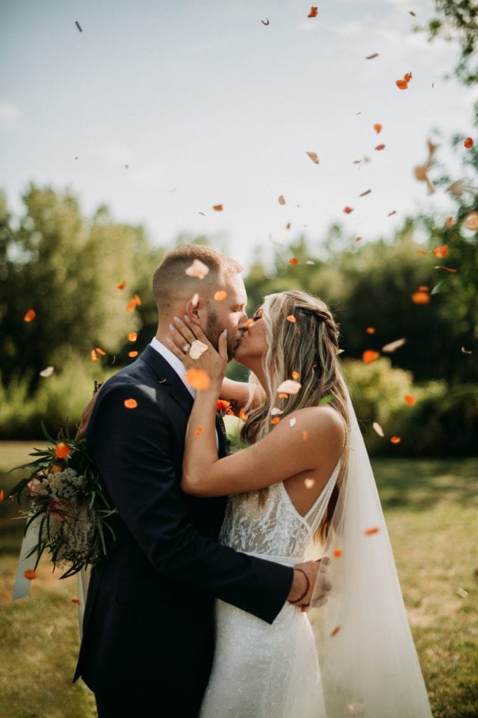 Bride and groom kissing while bridal party throws flower petals
