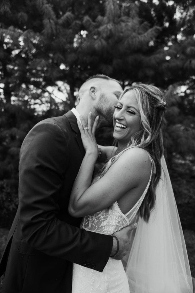 Groom kissing his bride's cheek and laughing right after their summer wedding ceremony at Mustard Seed Gardens
