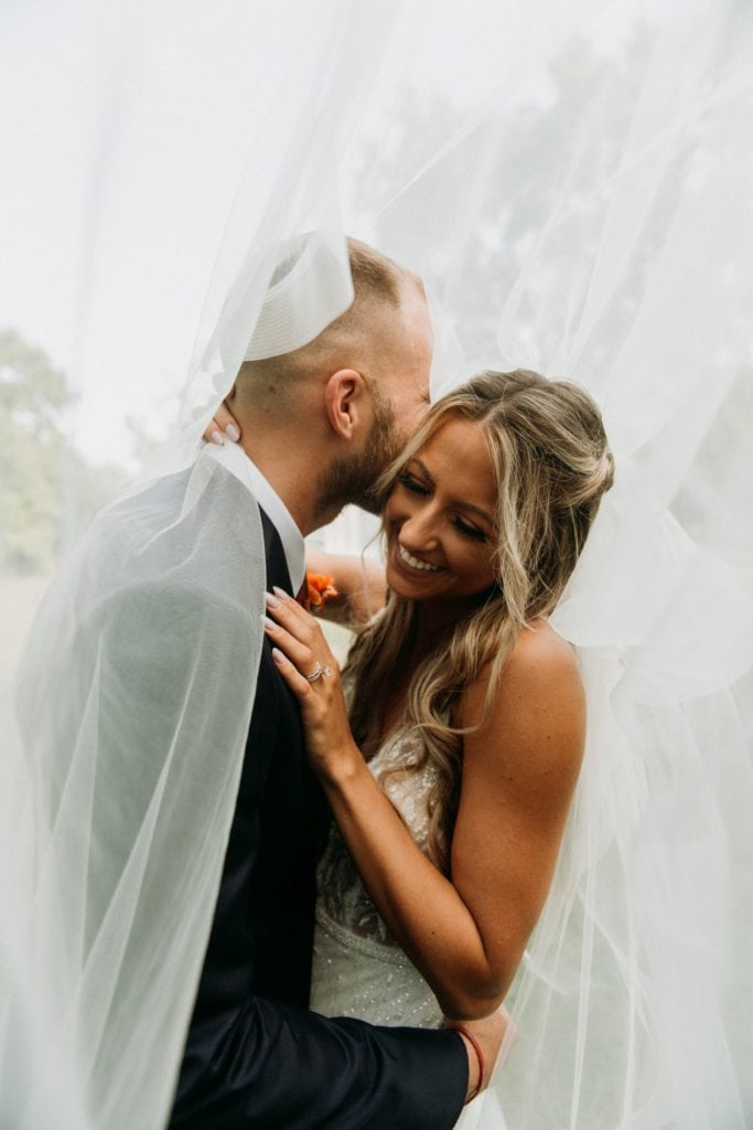 Bride and groom under a veil during their boho summer wedding