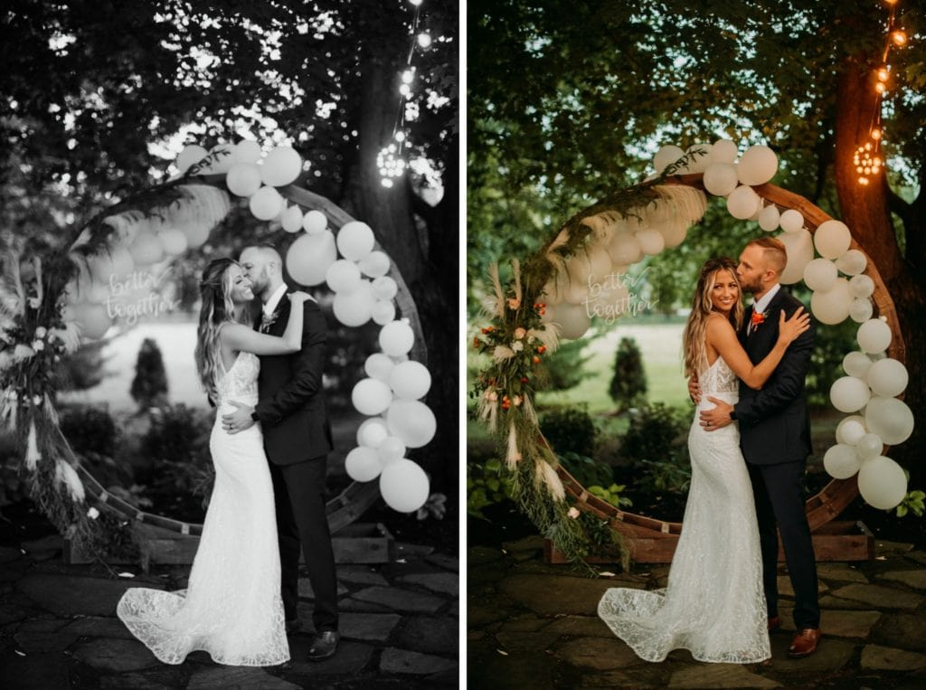 Groom kissing his brides cheek in front of a huge balloon arch that says better together at Mustard Seed Gardens