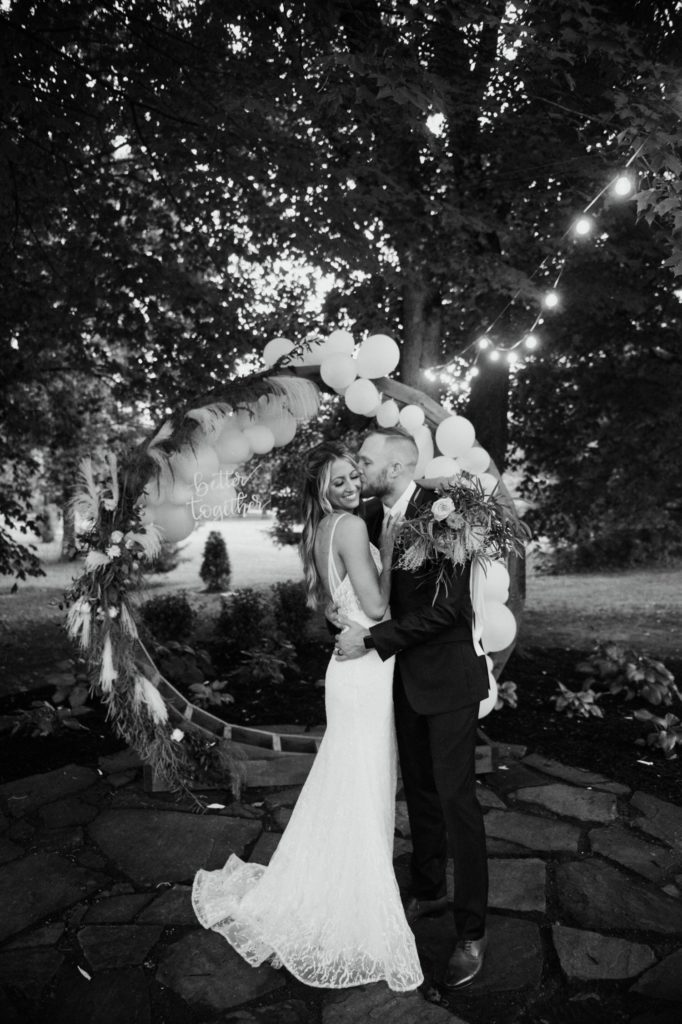 Bride and groom kissing in front of a huge balloon arch that says better together at Mustard Seed Gardens