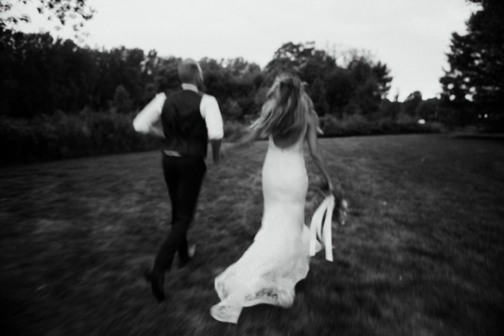 Bride and groom running through a field on their wedding day at Mustard Seed Gardens