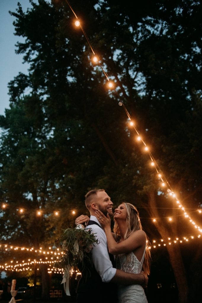 Bride and groom looking at each other underneath string lights at Mustard Seed Gardens