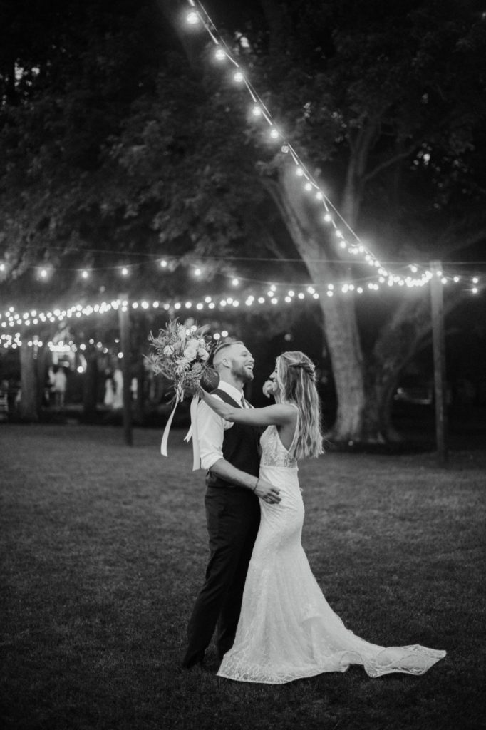 Bride and groom dancing and laughing underneath string lights at Mustard Seed Gardens