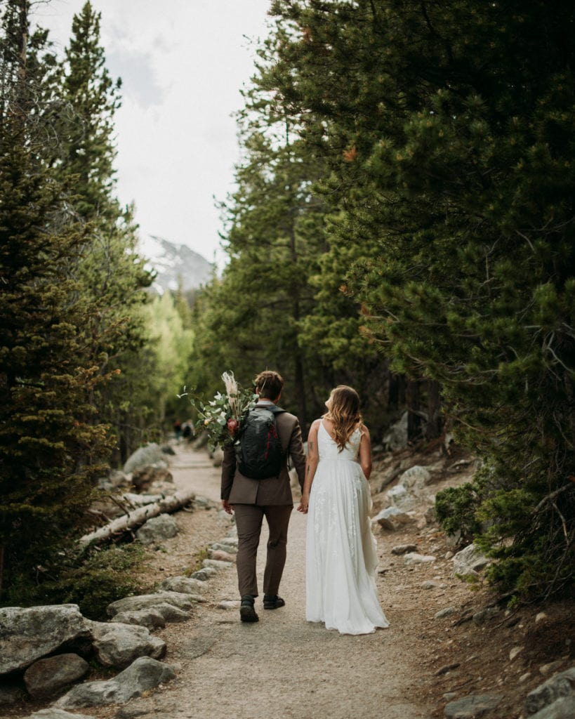 bride and groom hiking a trail to their ceremony site at rocky mountain national park