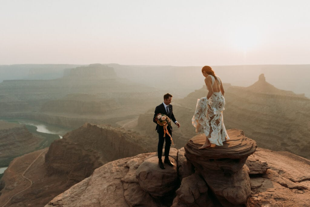 Bride and groom climbing on rocks in front of a canyon in moab utah. moab elopement photographer, how to elope in moab