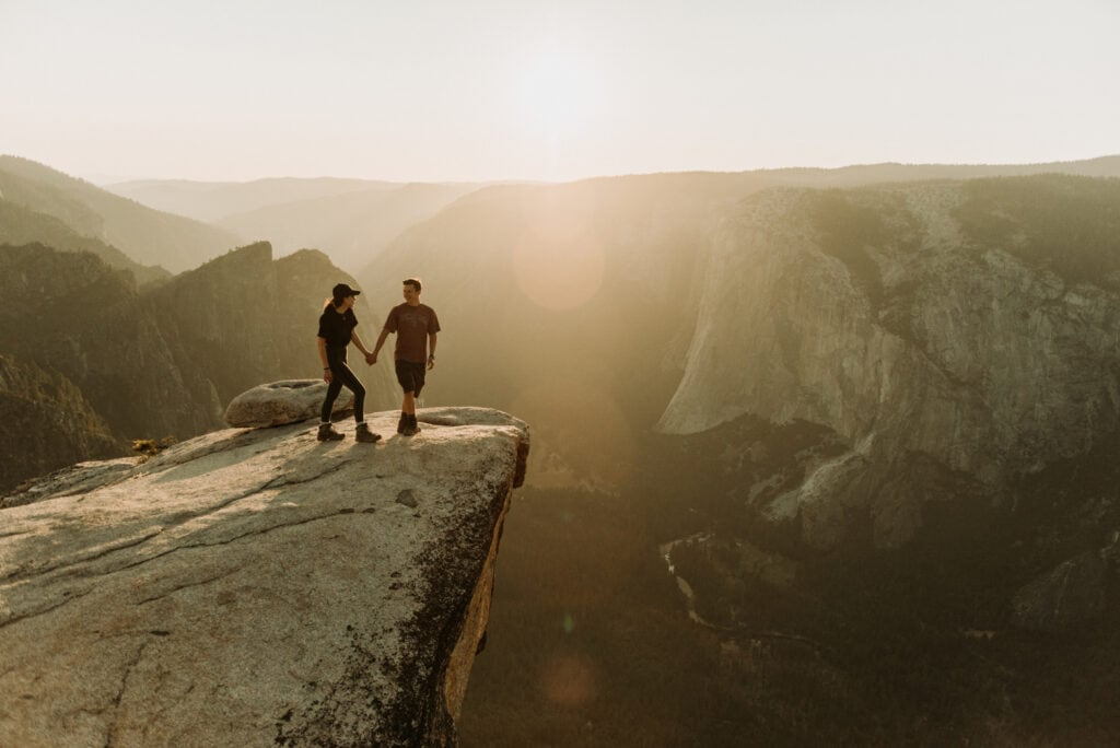 A couple walks towards the edge of a cliff admiring the views at Taft Point in Yosemite National Park.