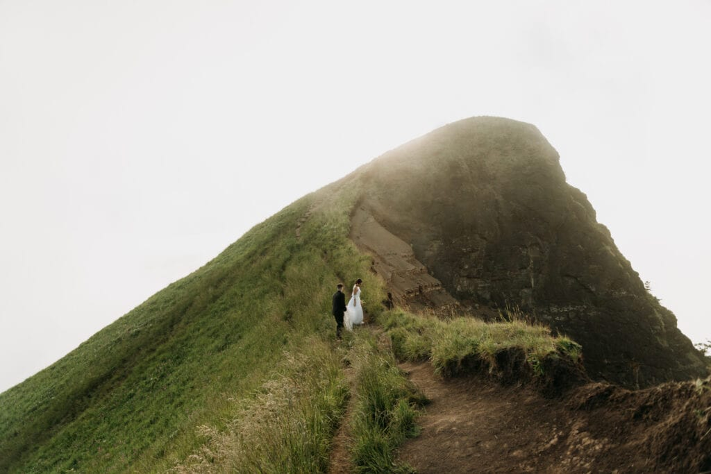 bride and groom hiking a mountain peak during their hiking elopement