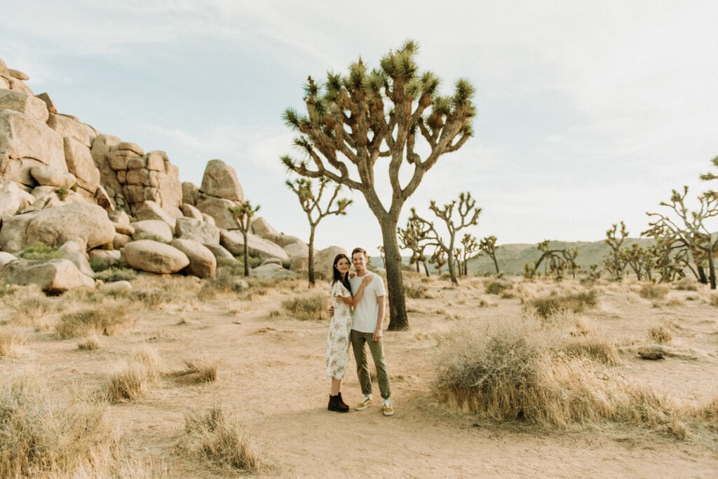 A couple smiling at the camera for their anniversary session in Joshua Tree california. Joshua tree national park engagement photos in the desert
