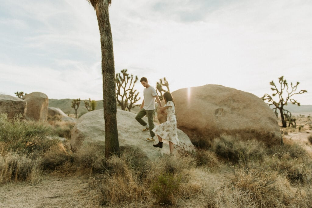 A couple running around in the desert for their anniversary session in Joshua Tree california. Joshua tree national park engagement photos at cap rock