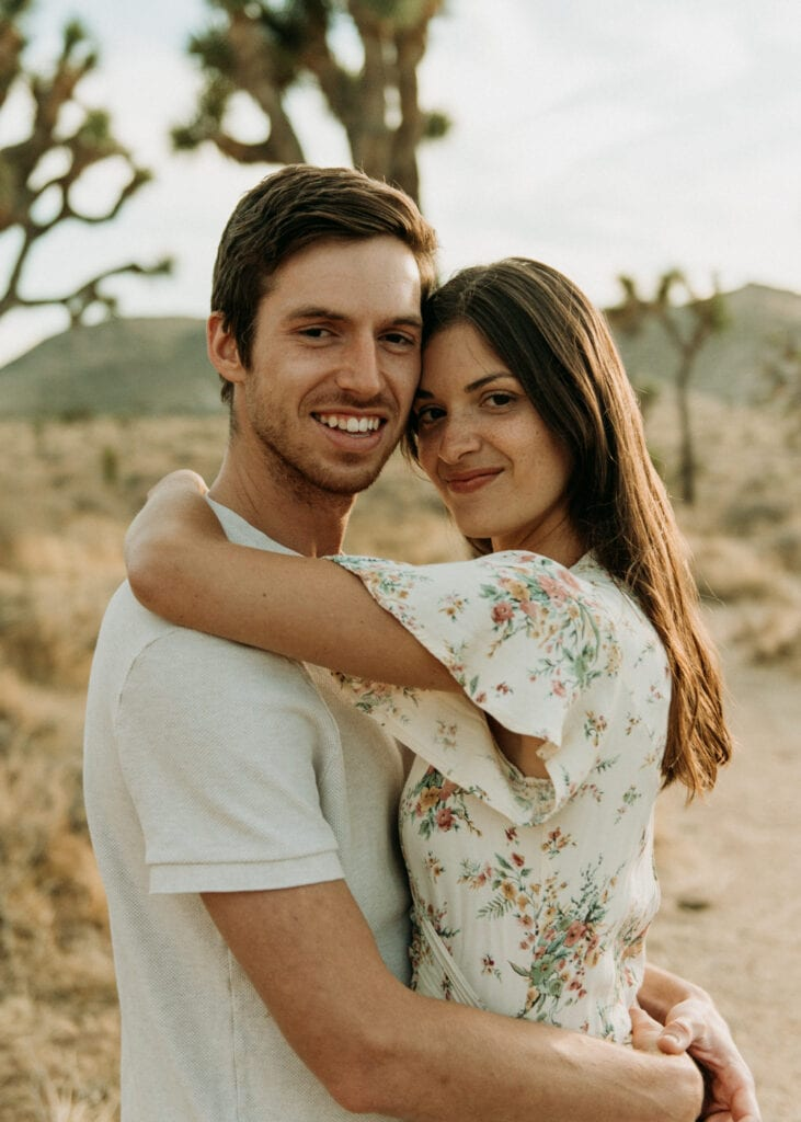 Married couple smiling at the camera  in the desert for their anniversary session in Joshua Tree california. Joshua tree national park engagement photos at cap rock