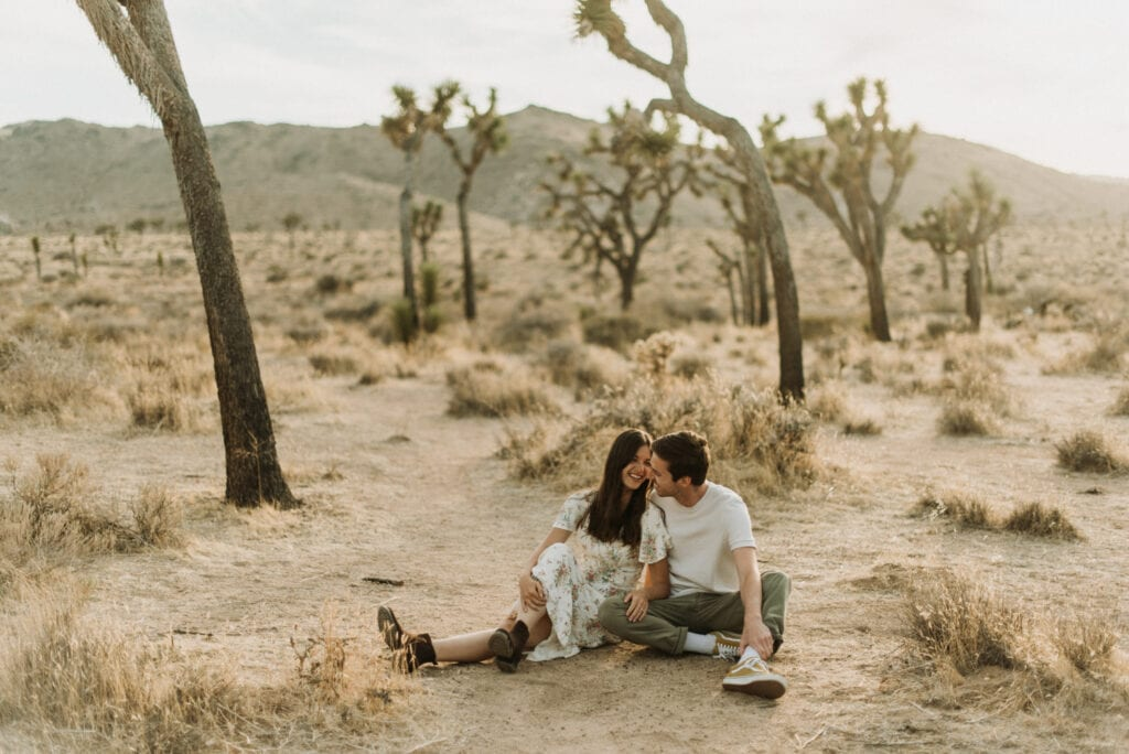 A couple sitting and laughing during their anniversary session in Joshua Tree california. Joshua tree national park engagement photos at cap rock