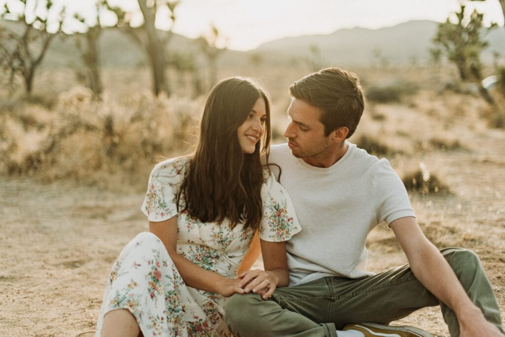 A couple snuggling during their anniversary session in Joshua Tree california. Joshua tree national park engagement photos at cap rock