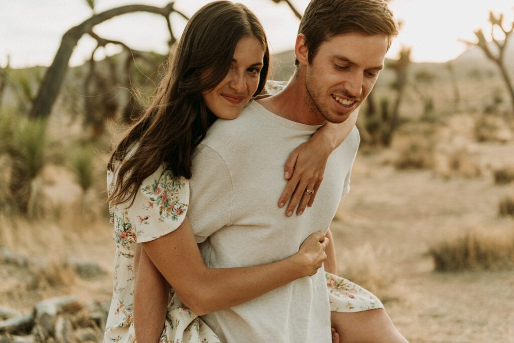 A woman getting a piggy back ride from her husband during their anniversary session in Joshua Tree california. Joshua tree national park engagement photos at cap rock