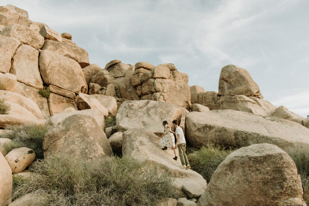 Couple climbing towards huge boulders in the desert during their anniversary session in Joshua Tree california. Joshua tree national park engagement photos at cap rock