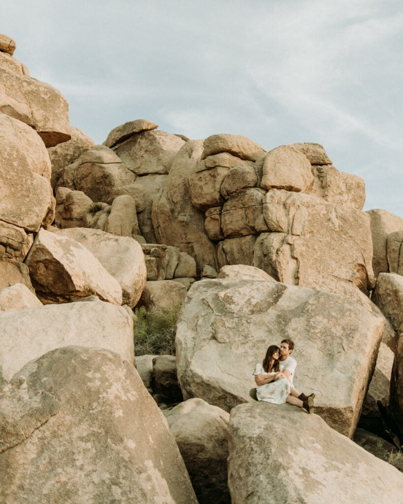 Couple sitting on huge boulders in the desert during their anniversary session in Joshua Tree california. Joshua tree national park engagement photos at cap rock
