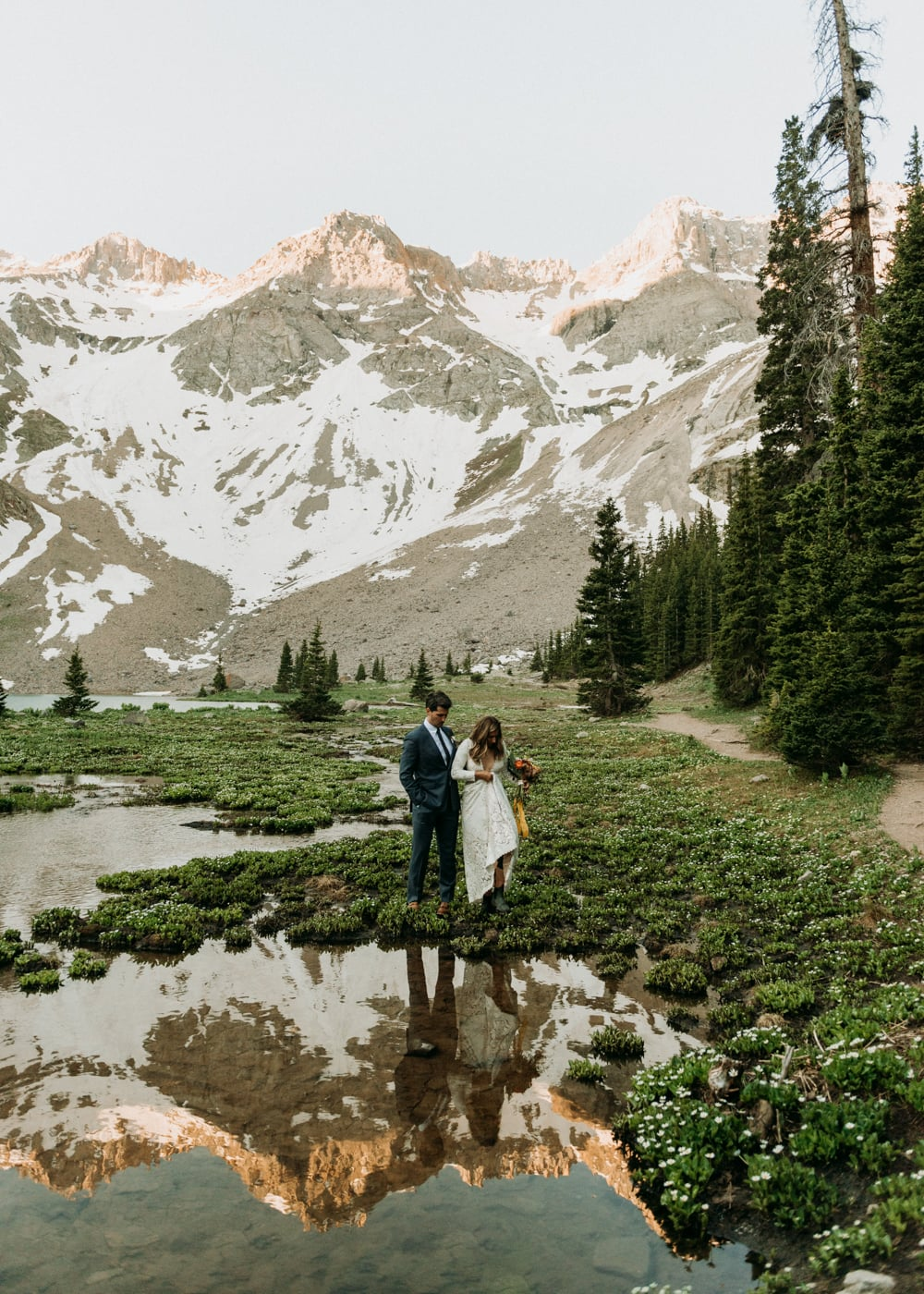 A couple walking through wildflowers in front of an alpine lake and mountains in Telluride, Colorado on their elopement day.