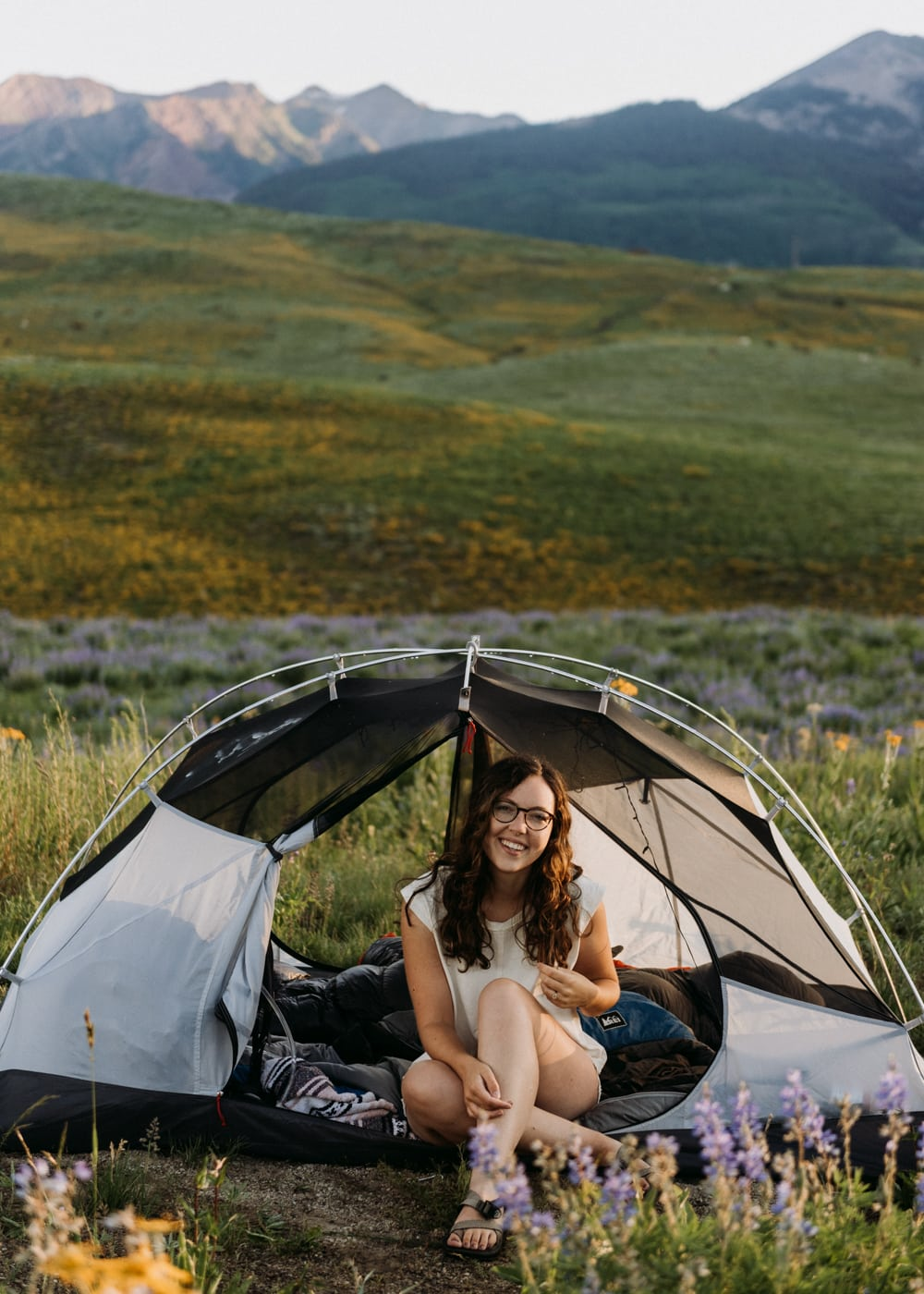 colorado elopement photographer sitting in a tent while camping in crested butte colorado